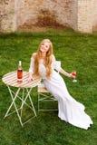 Вино красивой женщины выпивая в кафе outdoors Портрет молодой белокурой красоты в виноградниках имея потеху, наслаждаясь a Стоковая Фотография RF