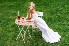 Вино красивой женщины выпивая в кафе outdoors Портрет молодой белокурой красоты в виноградниках имея потеху, наслаждаясь a Стоковое Изображение RF