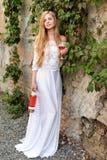 Вино красивой женщины выпивая outdoors Портрет молодой белокурой красоты в виноградниках имея потеху, наслаждаясь стеклом  Стоковая Фотография