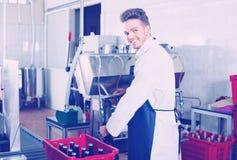 Вино мужского работника разливая по бутылкам с машиной на фабрике игристого вина Стоковое Изображение RF