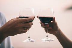 Вино питья пар на пляже захода солнца Стоковое фото RF