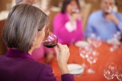 Вино пожилой женщины выпивая с друзьями стоковые фото