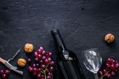 Вино подачи Бутылка, стекло, гайки и виноградина на черном copyspace взгляд сверху предпосылки таблицы Стоковые Фотографии RF
