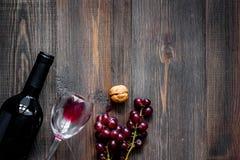 Вино подачи Бутылка, стекло, гайки и виноградина на copyspace взгляд сверху предпосылки деревянного стола Стоковые Изображения RF
