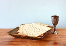 Вино предпосылки еврейской пасхи и хлеб еврейской пасхи matzoh еврейский над деревянной предпосылкой Стоковые Фотографии RF