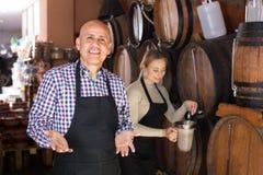 Вино продавца лить от деревянного бочонка Стоковая Фотография