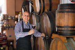 Вино продавца лить от деревянного бочонка Стоковые Фото