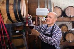 Вино продавца лить от деревянного бочонка Стоковое фото RF