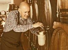 Вино продавца лить от деревянного бочонка Стоковые Изображения RF