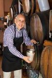 Вино продавца лить от деревянного бочонка Стоковые Фотографии RF