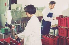 Вино работника разливая по бутылкам Стоковые Изображения