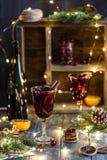 Вино рождества горячее обдумыванное в стекле со специями, цитрусовыми фруктами и клюквой Атмосфера рождества стоковая фотография