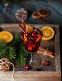 Вино рождества горячее обдумыванное в стекле со специями, цитрусовыми фруктами и клюквой Атмосфера рождества стоковые изображения rf