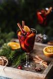 Вино рождества горячее обдумыванное в стекле со специями, цитрусовыми фруктами и клюквой Атмосфера рождества стоковое изображение