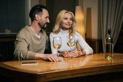 вино счастливых зрелых пар выпивая и смотреть прочь в гостинице Стоковая Фотография RF