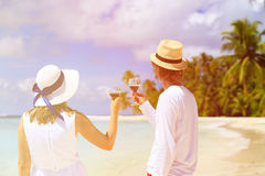 Вино счастливых любящих пар выпивая на пляже стоковая фотография