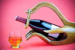 Вино с деревянной поддержкой на красной предпосылке Выпивать дальше празднует день Стоковая Фотография RF