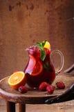Вино Sangrija в прозрачном кувшине на деревянном столе с Стоковое Изображение RF