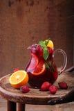 Вино Sangrija в прозрачном кувшине на деревянном столе с Стоковые Изображения