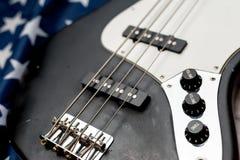 Винтажная басовая гитара на предпосылке американского флага стоковые фотографии rf