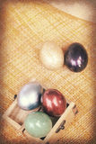 Винтажная бумажная текстура, красочные пасхальные яйца в деревянной коробке на бамбуковом weave Стоковое Изображение RF