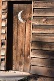Винтажная деревянная уборная во дворе с серповидной луной на двери стоковые фотографии rf