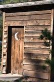 Винтажная деревянная уборная во дворе с серповидной луной на двери стоковые изображения rf