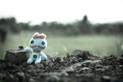 Винтажная злая пугающая кукла сидит на поле Стоковые Изображения RF
