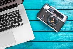Винтажная камера и компьтер-книжка фото на деревянном столе стоковая фотография