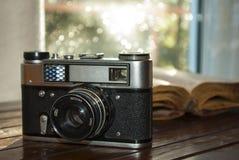 Винтажная камера и старая книга на таблице Стоковые Фото