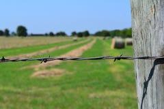 Винтажная колючая проволока ограждая вокруг поля сена Стоковое Изображение