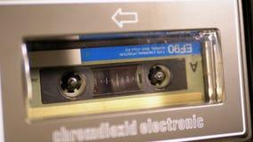 Винтажная магнитофонная кассета в магнитофоне играя и вращает видеоматериал