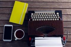Винтажная машинка, дневник, черный кофе и умный телефон на деревянном столе Стоковое фото RF