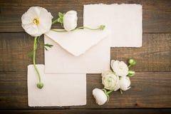 Винтажная предпосылка сделанная из бумажных открыток, конверта и белых цветков на деревянной предпосылке Плоское положение, взгля Стоковое фото RF