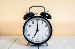 Винтажная предпосылка с ретро будильником 7pm am на деревянном столе Стоковое фото RF