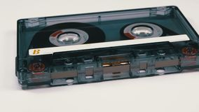 Винтажная прозрачная магнитофонная кассета вращает на белой предпосылке сток-видео