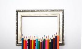 Винтажная рамка для картин и покрашенных карандашей на белой предпосылке стоковое фото rf