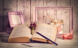 Винтажная рамка, лампа ночи и куча бумаги на белой винтажной таблице Стоковая Фотография RF