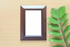 Винтажная рамка фото на деревянном поле и зеленых лист ветви p Стоковые Изображения RF