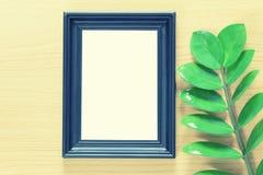 Винтажная рамка фото на деревянном поле и зеленых лист ветви p Стоковые Фото