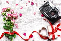 Винтажная ретро камера с розовым букетом роз, красной лентой и подарочной коробкой Стоковые Изображения