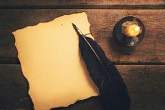Винтажная ручка пера и пустая старая бумага в свете горящей свечи Стоковое фото RF
