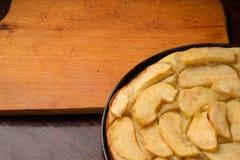 Винтажная старая разделочная доска на деревянной предпосылке около яблочного пирога, места для текста на деревянной деревенской п Стоковые Фото