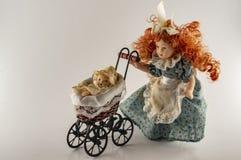 Винтажная терракотовая кукла с pram и ребенком стоковая фотография