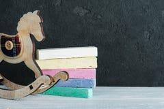 Винтажная тряся лошадь рядом с черной доской Стоковое Фото