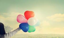 Винтажная форма воздушного шара сердца с красочным в руке на ландшафте в лете Стоковые Фото