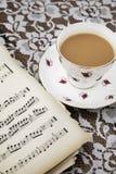 Винтажная чашка чая, поддонник и музыкальные листы Стоковые Фото