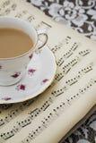 Винтажная чашка чая, поддонник и старые музыкальные листы Стоковое фото RF