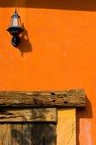 Винтажная электрическая смертная казнь через повешение лампы фонарика на оранжевой бетонной стене стоковые изображения
