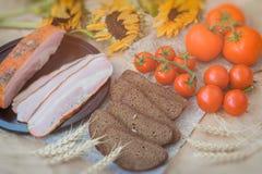 Винтажное взгляд сверху Очень вкусные куски бекона, хлеба рож черного, зрелых красных томатов на дерюге, старом взгляд сверху сол Стоковая Фотография RF